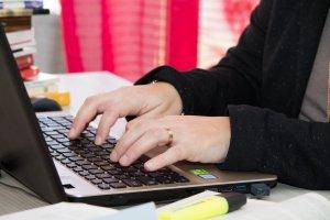 Le mani della ghostwriter Donatella Briganti che scrivono su un PC