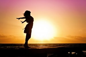 Donna in riva al mare al tramonto a braccia aperte