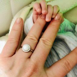 Dettaglio di un bellissimo anello con latte materno realizzato da Marina D'Avanzo nella mano di una mamma che sfiora quella del suo bimbo