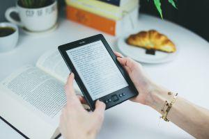 mani che tengono un tablet con ebook e sfondo di libri, tazze e un croissant