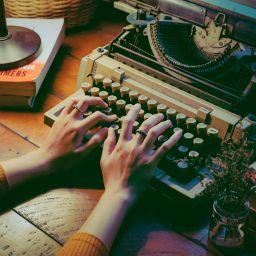 mani che scrivono su una macchina da scrivere