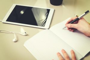 mani che scrivono con accanto un tablet